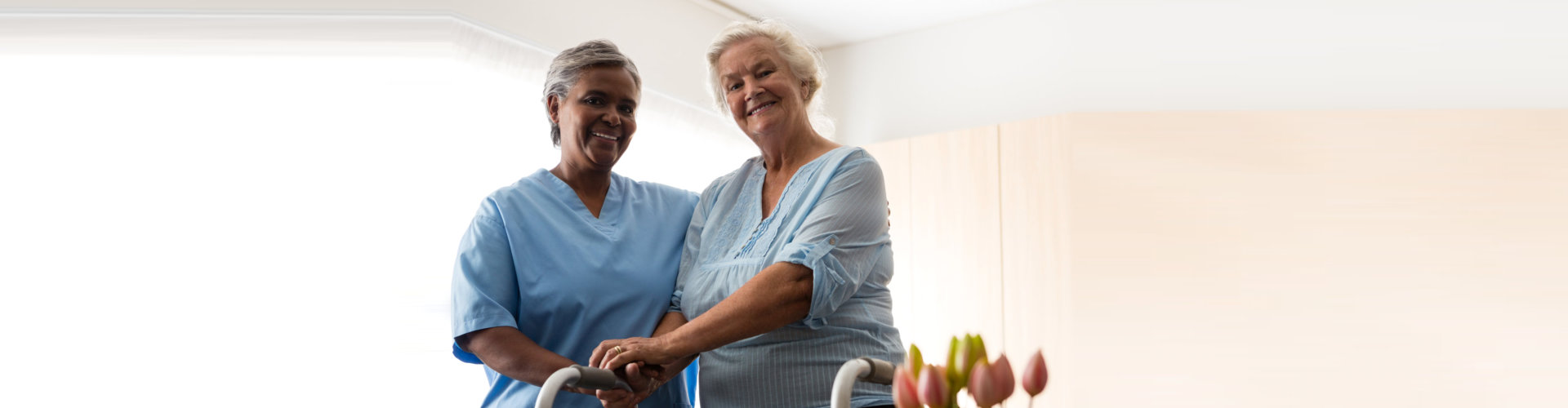 caregiver and senior woman smiling at the camera