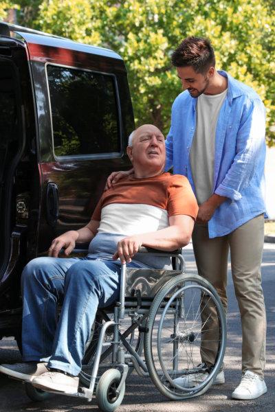 caregiver assisting senior man in a wheelchair
