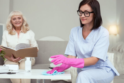 senior patient smiling while a caregiver is cleaning