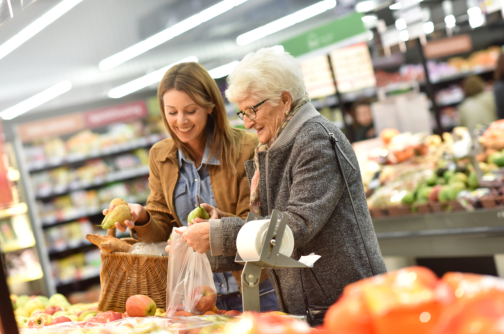 woman and senior patient smiling while buying fruits