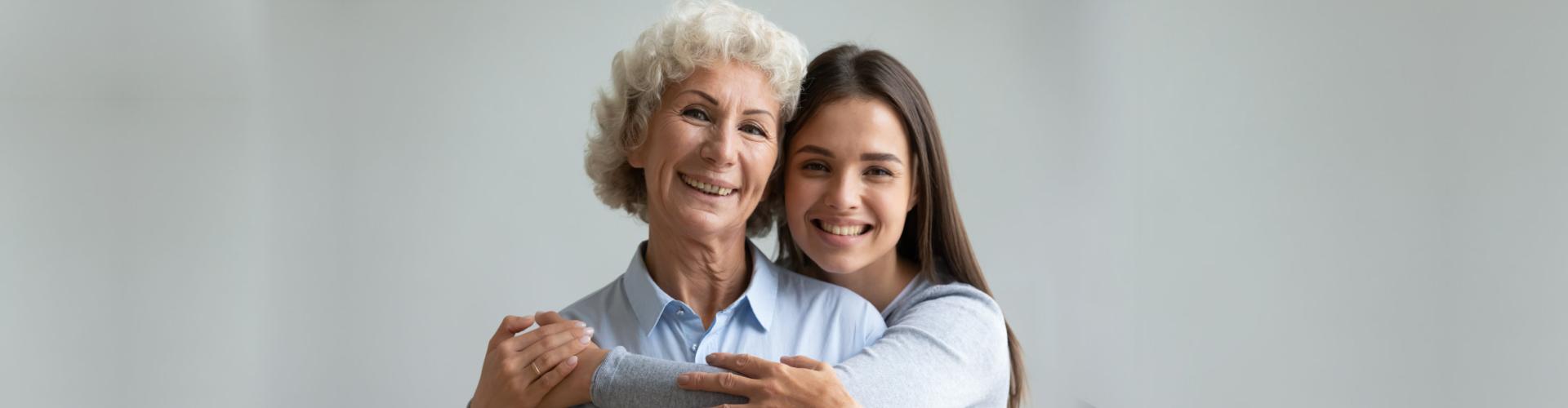 female caregiver hugging senior woman while smiling