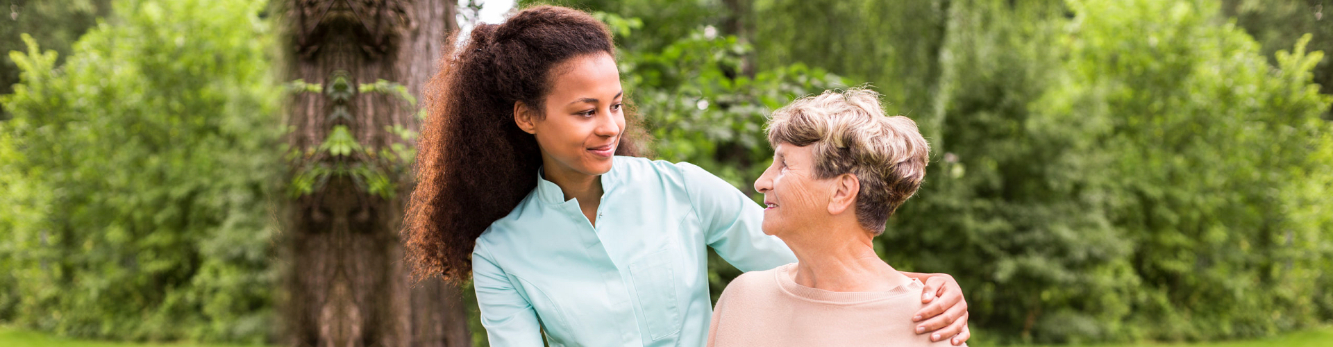 female caregive and senior woman smiling outdoor