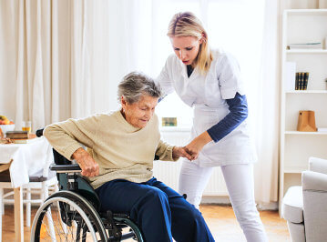 female caregiver assisting senior woman to stand