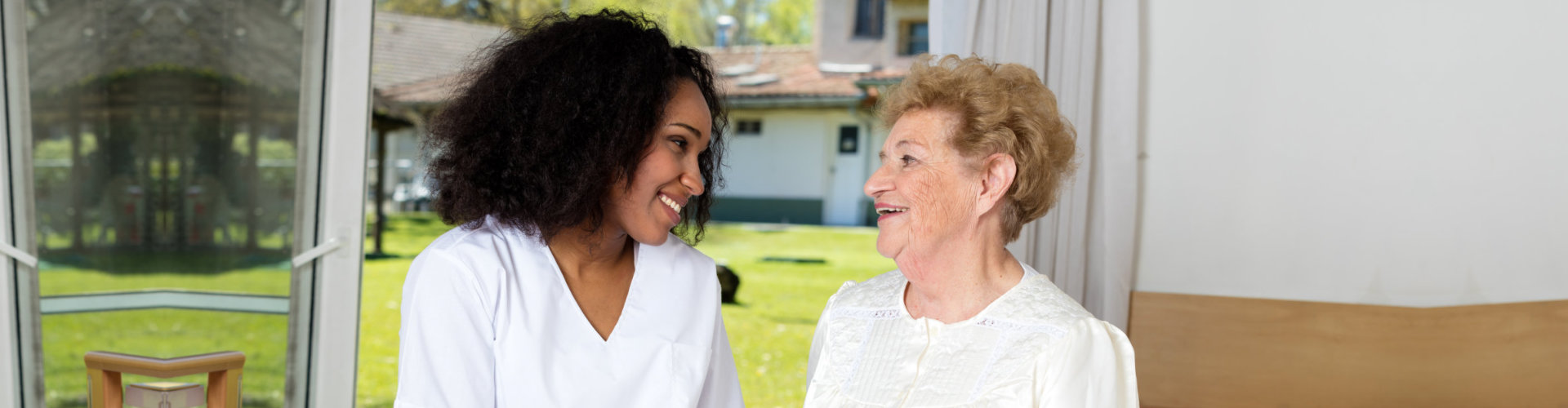 caregiver looking at the senior woman whie smiling